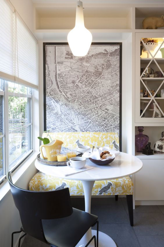 a modern bold breakfast nook by the window done in grey and yellow and with a map mural on the wall