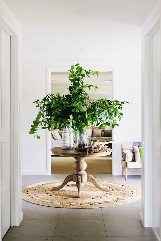 a round pedestal table in the center of the room with greenery in a vase and some wood works as a display table