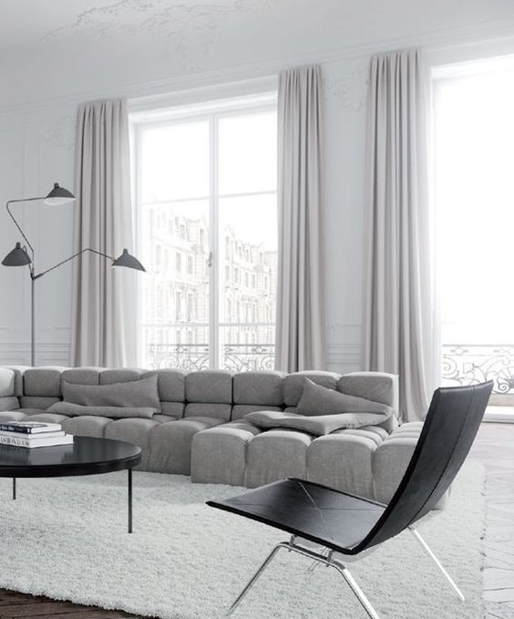a stunning minimalist space with a statement grey upholstered sof and lilac curtains