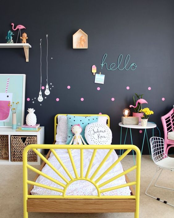 a colorful space is calmed down with a black statement wall, which is made more cheerful with bold accessories