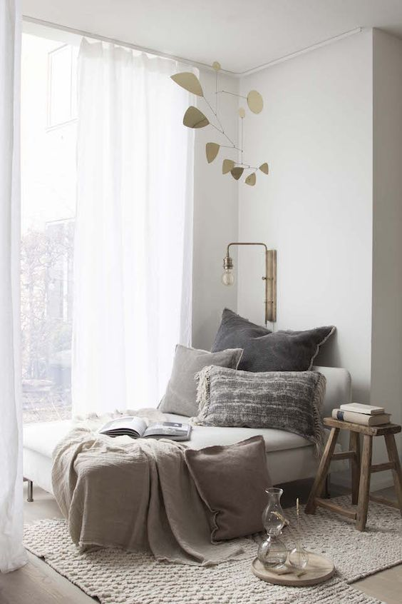 a cozy and natural nook with a daybed, lots of pillows, comfy rugs and a wood stool