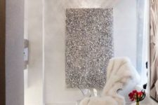 20 a shiny silver stool or table, a faux fur rug and blanket and a shiny artwork on the wall