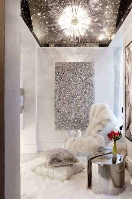 a shiny silver stool or table, a faux fur rug and blanket and a shiny artwork on the wall