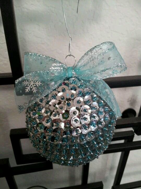 a silver and light blue sequin ball ornament with a large light blue ribbon bow