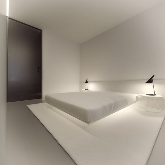 a very clean minimal bedroom with a floating bed and additional lighting under it