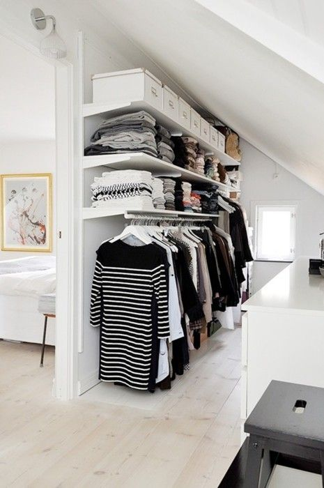 an awkward attic corner is taken by a makeshift closet with open shelving and hangers