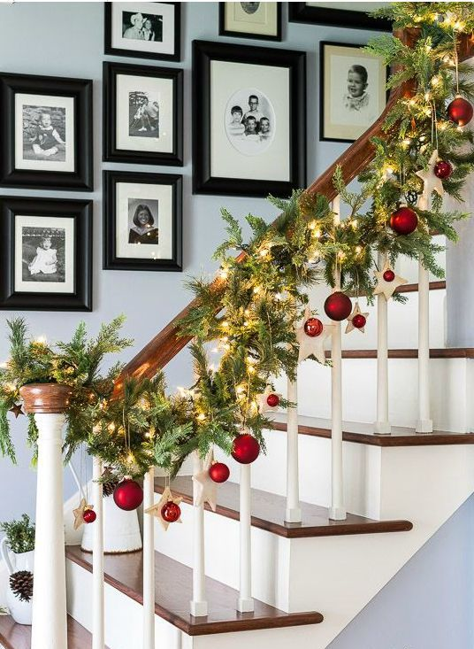 an evergreen garland with lights, stars and red ornaments to line up the stairs