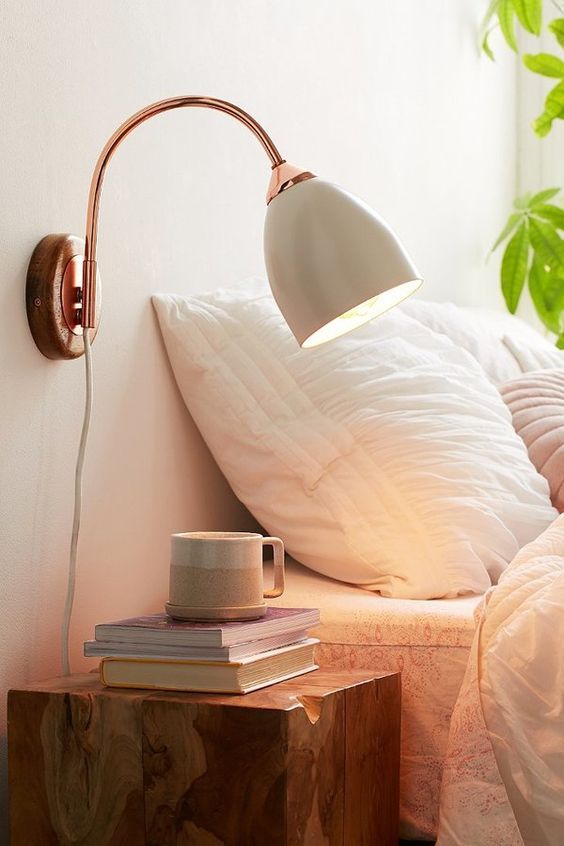 a chic sconce with a copper base and tube, a neutral flower-inspired lampshade for a romantic touch