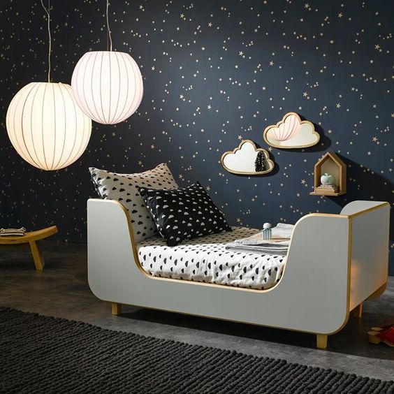 a dreamy bedroom with a black starry wall and matching sky-inspired bedding