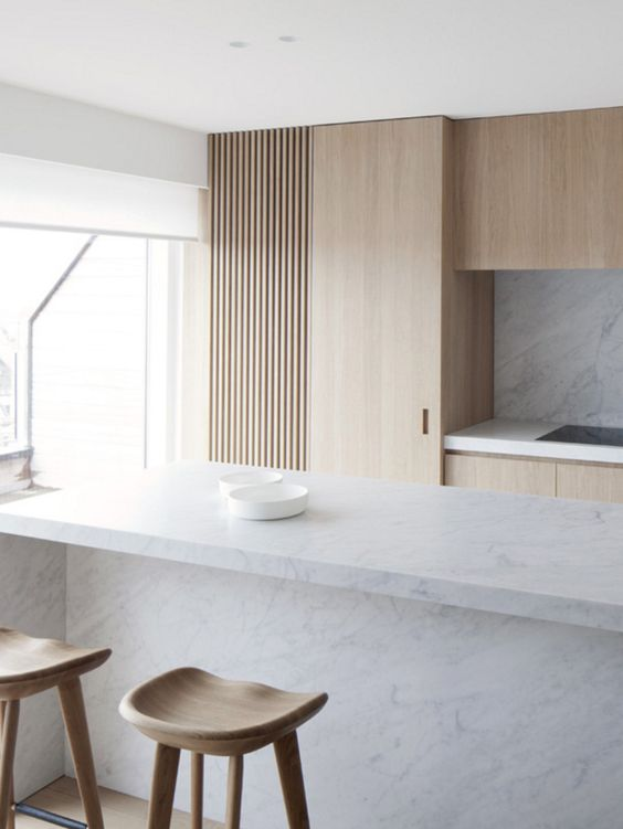 a minimalist kitchen is done with light-colored wood and marble to make it more interesting