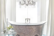 21 a shiny silver clawfoot bathtub and a glam chandelier over it will make your bathroom super cute