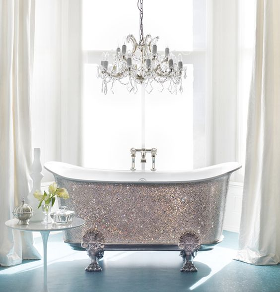a shiny silver clawfoot bathtub and a glam chandelier over it will make your bathroom super cute