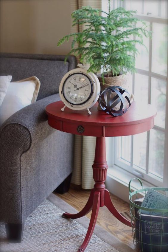 a small vintage red pedestal table with some pretty items on display will be a great side table