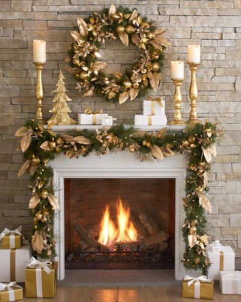 an evergreen and gold fruit and leaf garland and wreath for a holiday fireplace