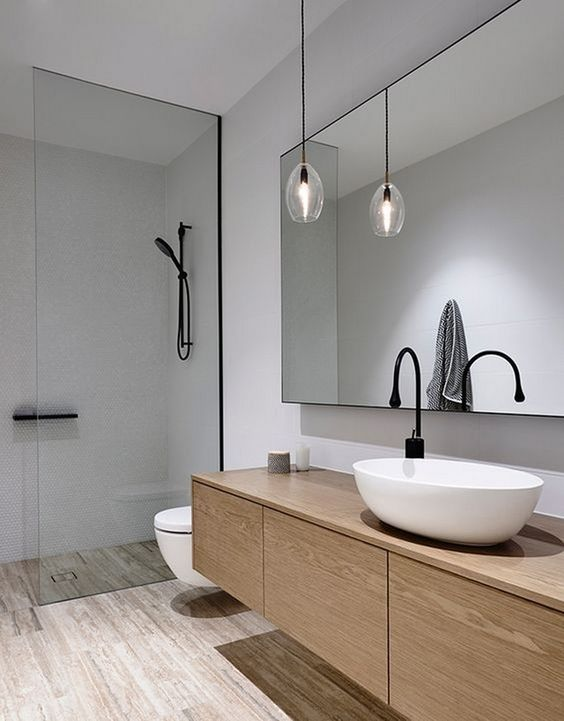 a bathroom is warmed up with a wood vanity and floor to make it cooler