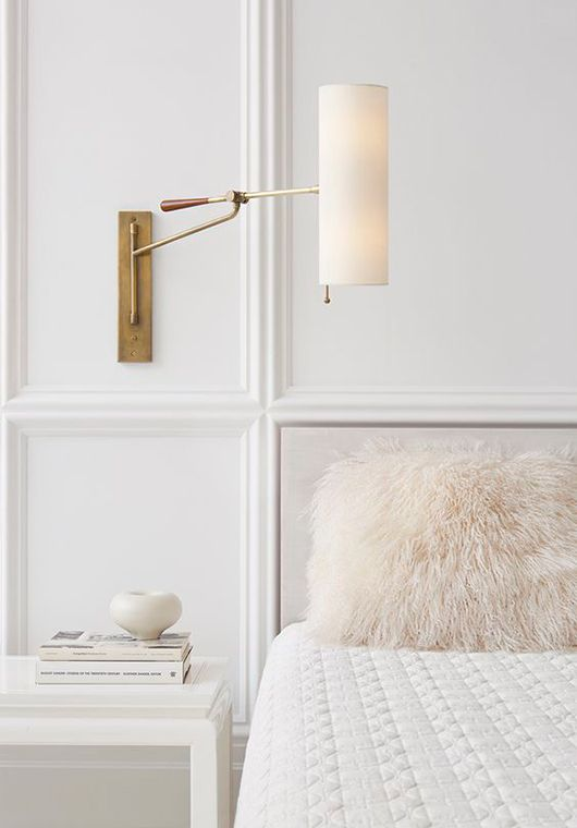 a chic sconce with a tube shadde and a brass base looks very elegant