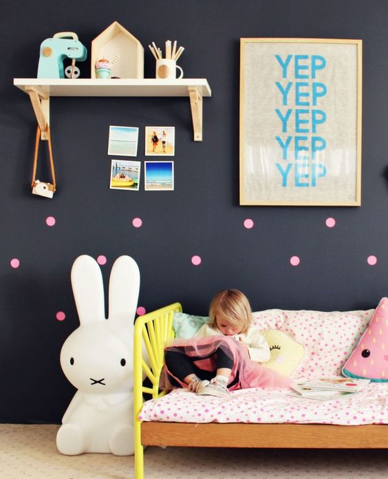 a girl's room can be done with a black wall, too, add some cute touches like pink dots, artworks and photos