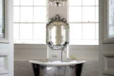 22 a shiny silver free-standing bathtub, a matching vintage mirror and a crystal chandelier