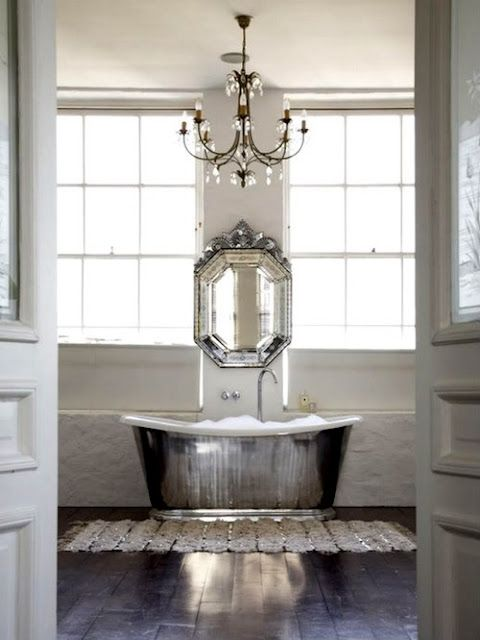 a shiny silver free-standing bathtub, a matching vintage mirror and a crystal chandelier