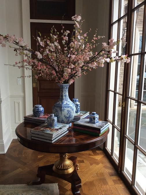 a vintage rich-colored wood table serves as a display for books and blue china and makes th einterior refined