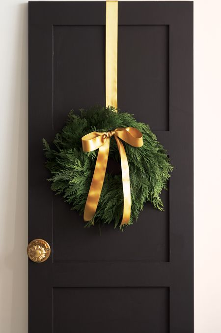 an evergreen wreath with gold ribbon and a bow looks natural and very cute