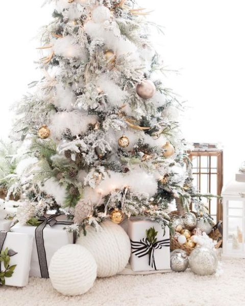 a gorgeous flocked Christmas tree with metallic ornaments of various shades and pinecones
