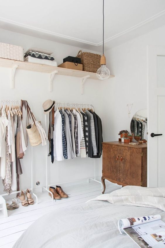 a makeshift closet in a serene bedroom takes one wall and there's much storage space