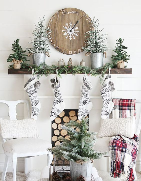 black and white stockings, snowy evergreen trees, an evergreen garland and a wooden Christmas clock