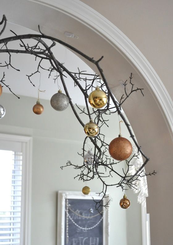 decorate an archway with branches and mixed metal ornaments of different sizes and looks