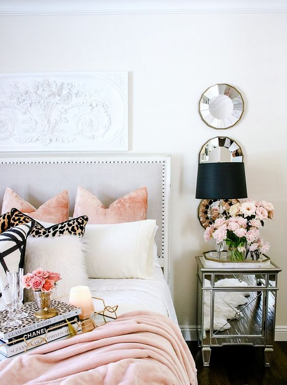 a chic mirrored nightstand and some round mirrors make the bedroom more feminine and shiny