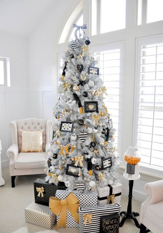 a modern glam Christmas tree with gold, black and white decor and ornaments, letters and feathers