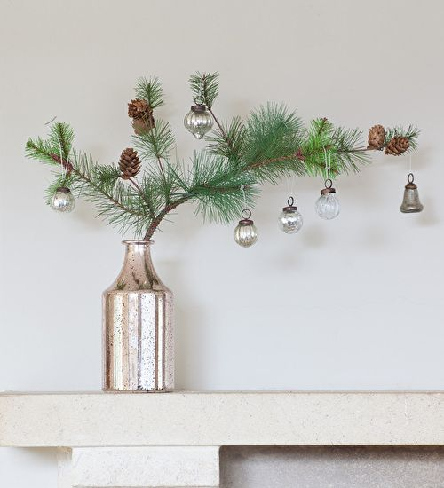 a pine branch with pinecones and some vintage ornaments in a single stem vase
