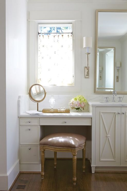 a small beauty nook in the bathroom located next to the window and a lamp over it