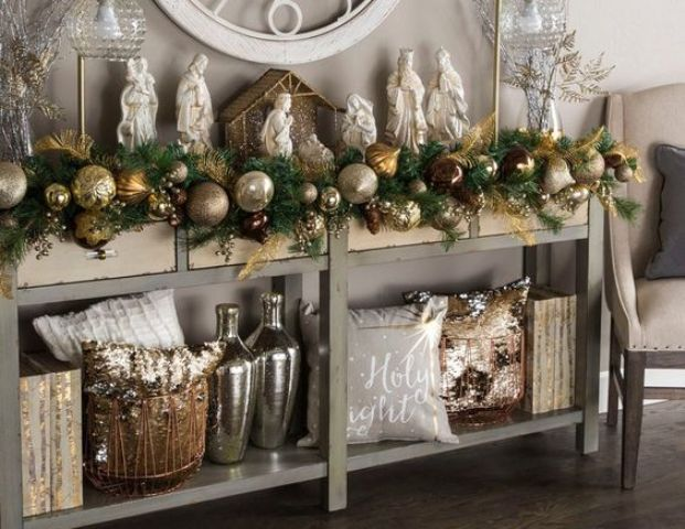 an evergreen garland with gold, copper and silver large ornaments is great for decorating a console