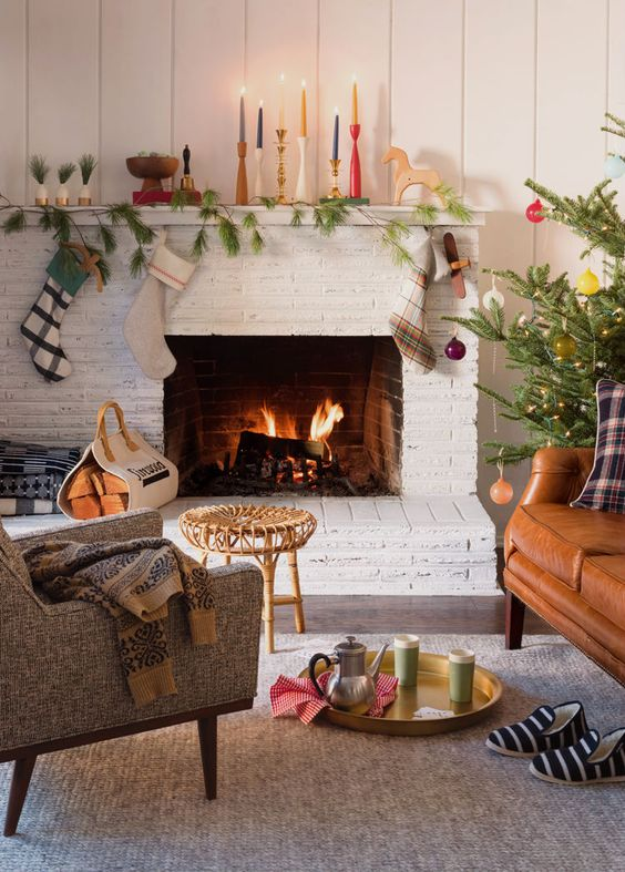 colorful candles, a pine garland, some plaid stockings and ornaments is a simple arrangement to make