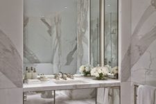 24 light-colored marble and a built-in mirrored vanity and mirrors on three sides