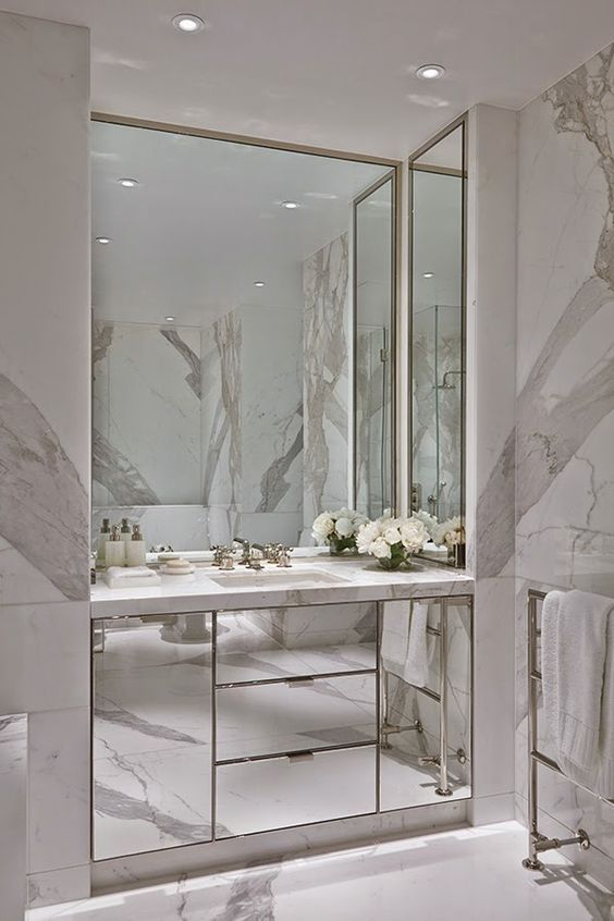 light-colored marble and a built-in mirrored vanity and mirrors on three sides
