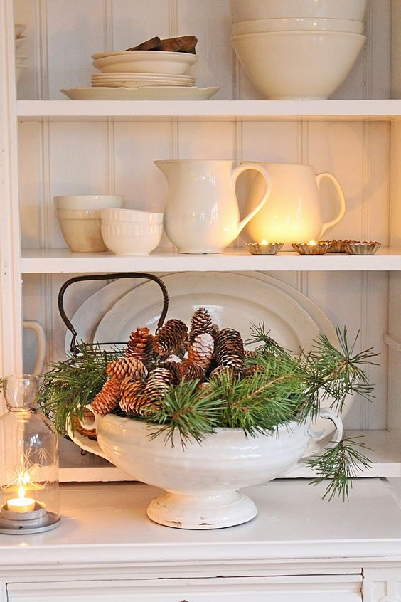 a soup bowl with evergreens and pinecones is ideal for cozy rustic decor in the kitchen