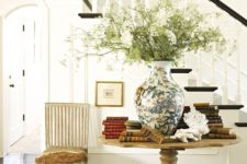 25 a vintage wooden pedestal table with lots of books and a large vase with greenery looks wow