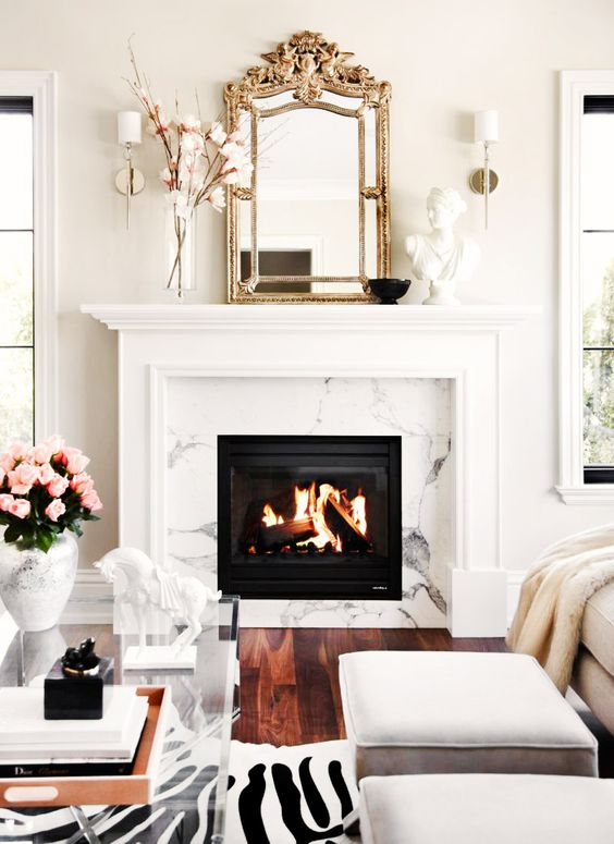 a glam clad fireplace, a zebra print rug, a vintage mirror and an acrylic table to add a refined glam feel