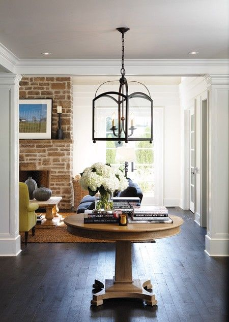 a wood pedestal table with books and a vase serves a great eye-catchy piece