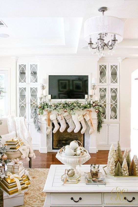 neutral stockings, a snowy evergreen garland with copper ornaments and candles for a chic look