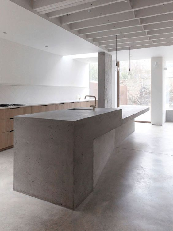 a large sculptural concrete kitchen island and wooden cabinets for a minimal ktichen