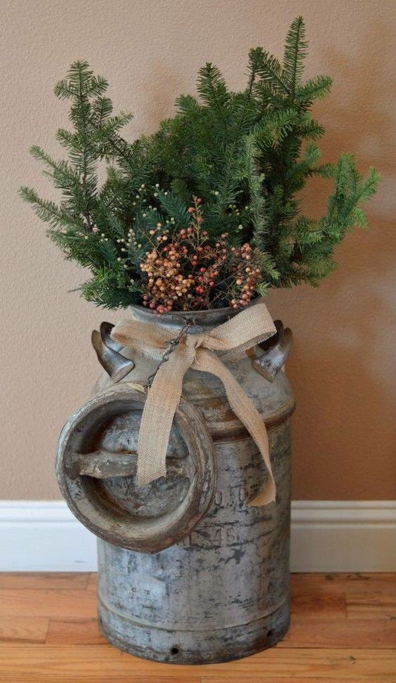 a vintage milk churn with a burlap bow, evergreen branches and berries for outdoor decor