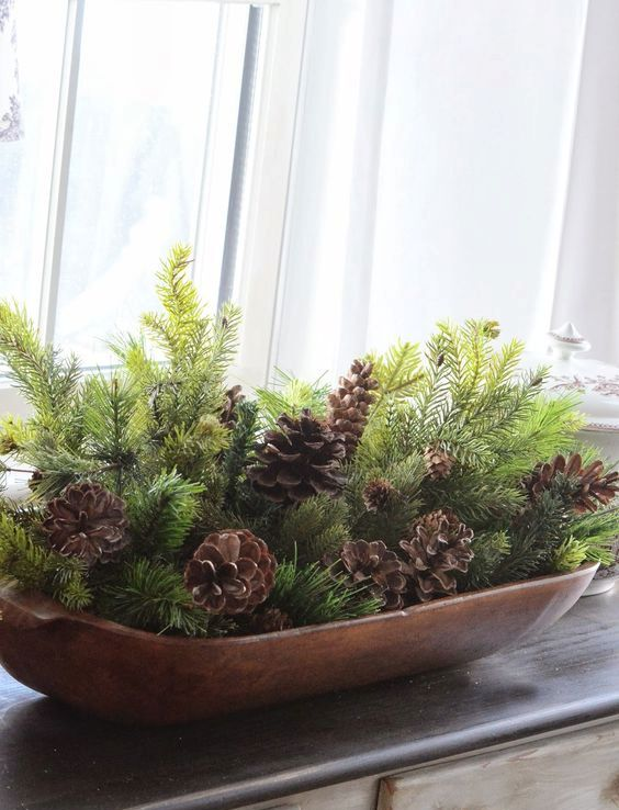 a wooden bread bowl with evergreens and pinecones for a simple rustic display