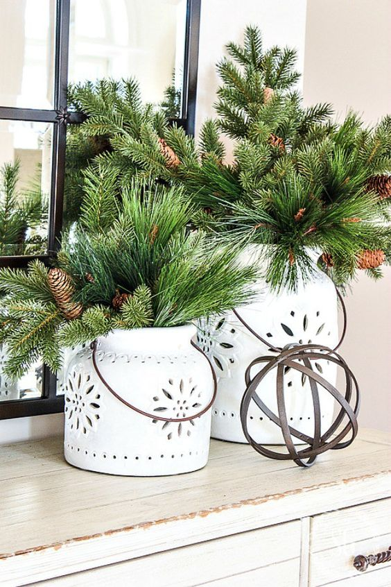 white candle lanterns with faux evergreens and pinecones for a rustic winter feel