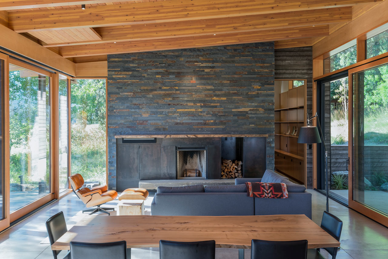 The beautiful living room features a large reclaimed wood clad fireplace and glazed walls from both sides to catch the views