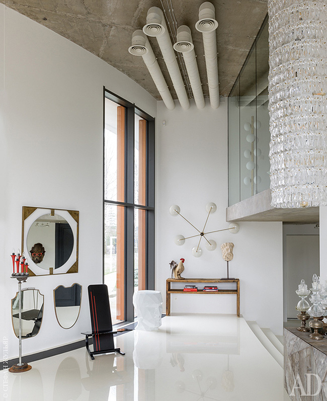 The entryway of this home strikes with arworks, an oversized crystal chandelier and eye catchy mirrors