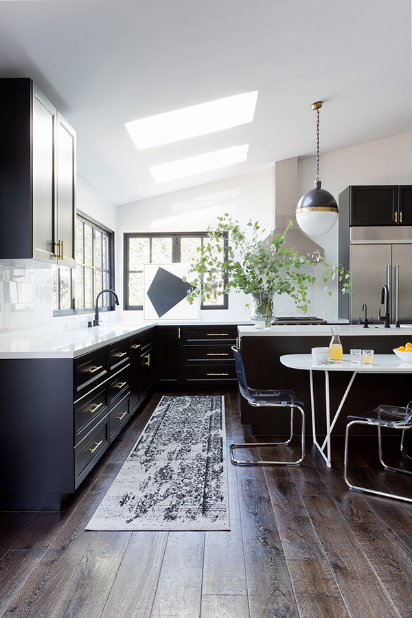 The kitchen is done in the classic color palette of black and white, with skylights and windows to bring natural light in