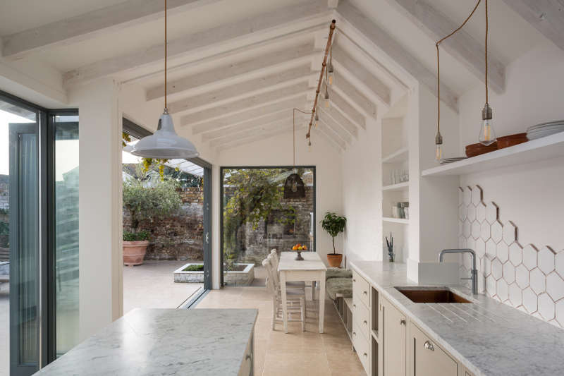 This airy white kitchen and dining zone is opened to outdoors as much as possible and feels very light and airy